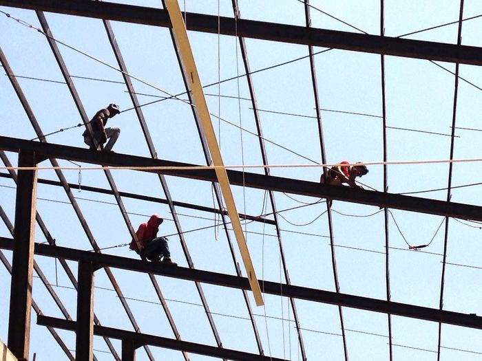 Low Angle View Of Men Working On Construction Frame