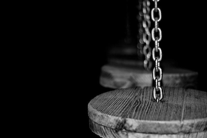 Close-up of wood hanging to chains against black background