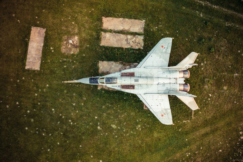 High angle view of airplane flying over field