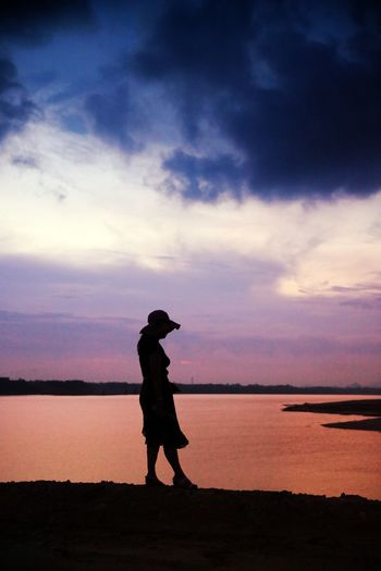 Silhouette woman standing by river during sunset
