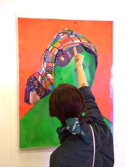 Rear view of woman standing against multi colored wall