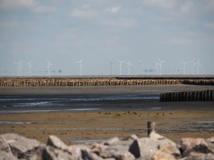 No Filter Wind Turbine Wind Power Alternative Energy Renewable Energy Power In Nature Electricity  Sustainable Resources Mud Mud Flat Ebb And Flow Ebb Ebb Tide Stonestructures Horizon Shimmer Zoom Shot No People Wooden Structure Wooden Wall