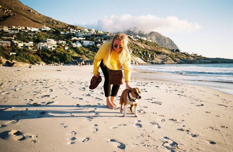 Portrait of woman with dog at beach