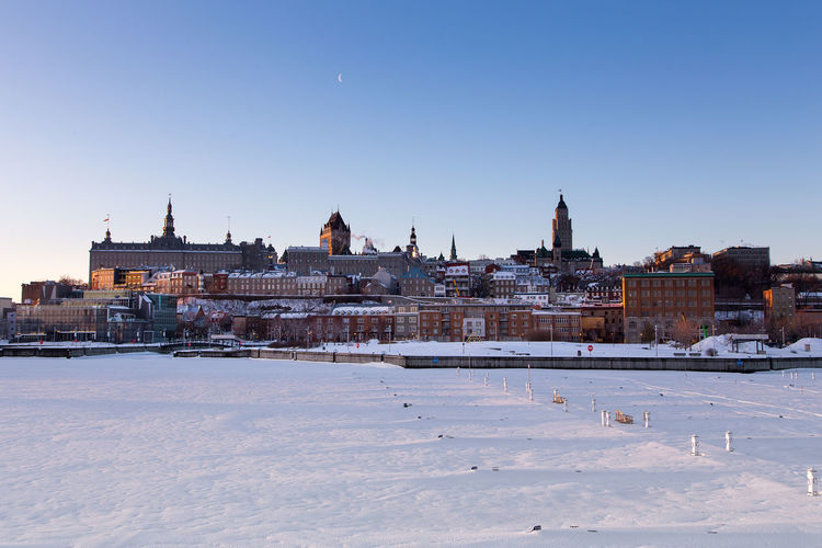 Snow covered buildings in city against clear sky