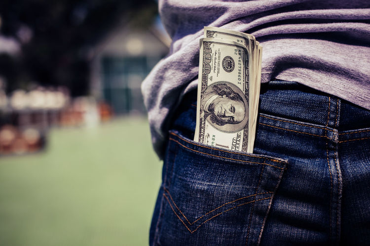 Close-up of us paper currency in jeans pocket