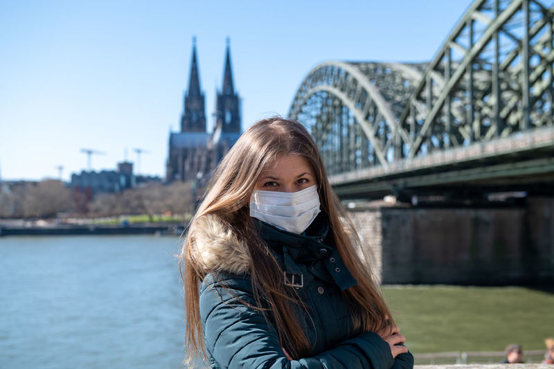 Portrait of young woman wearing mask standing against bridge over river