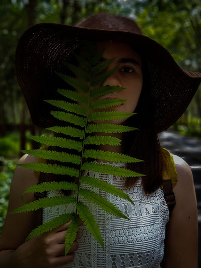 Close-up portrait of woman holding fern leaves