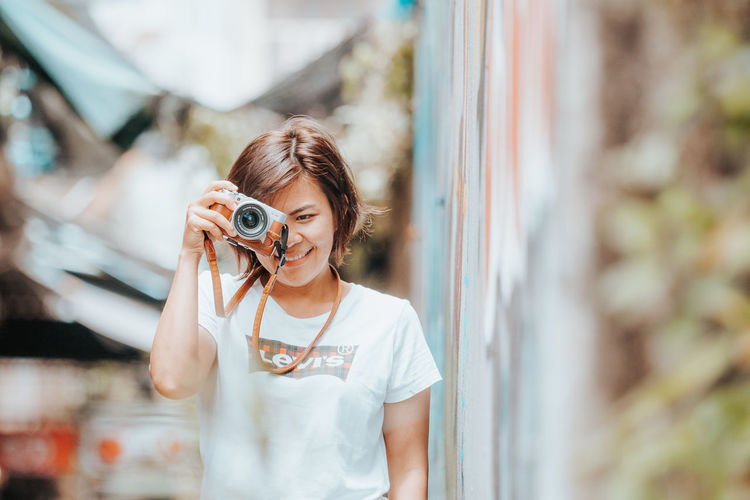 Portrait of woman holding camera while standing outdoors