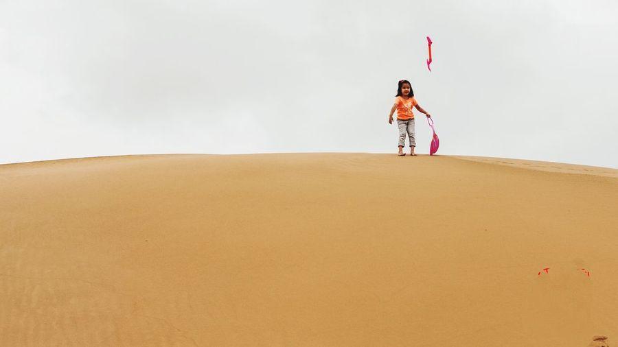 Full length of girl throwing shovel while standing on sand dune against sky