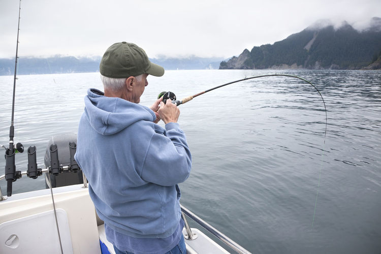 Senior fisherman reeling in a fish in the ocean near Seward, Alaska Rod One Person Leisure Activity Fishing Water Outdoors Senior Adult Boat Salmon Halibut Ling Cod Ocean Sea Alaska Seward Alaska Catching Reel Middle Aged Man Caucasian Color Image Photography Real People Hills Clouds Cap