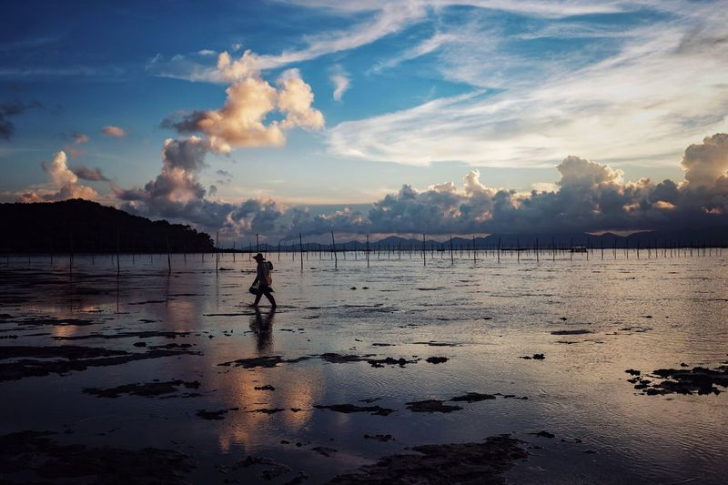 Sky Beach Water Cloud - Sky One Person Reflection Tranquil Scene Beauty In Nature Tranquility Sea Scenics Nature Real People Sand Outdoors Sunset Full Length Day People Live For The Story Out Of The Box The Street Photographer - 2017 EyeEm Awards The Great Outdoors - 2017 EyeEm Awards The Photojournalist - 2017 EyeEm Awards EyeEmNewHere
