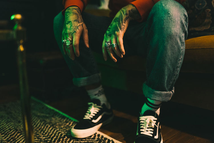 Hands Body Part Casual Clothing Focus On Foreground Front View Green Color Human Body Part Human Leg Indoors  Jeans Leisure Activity Lifestyles Low Section Men Night Nightlife One Person Real People Relaxation Shoe Sitting Sport Tattoo Tattoos Vans