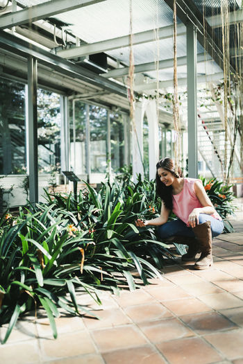 Woman sitting by plants