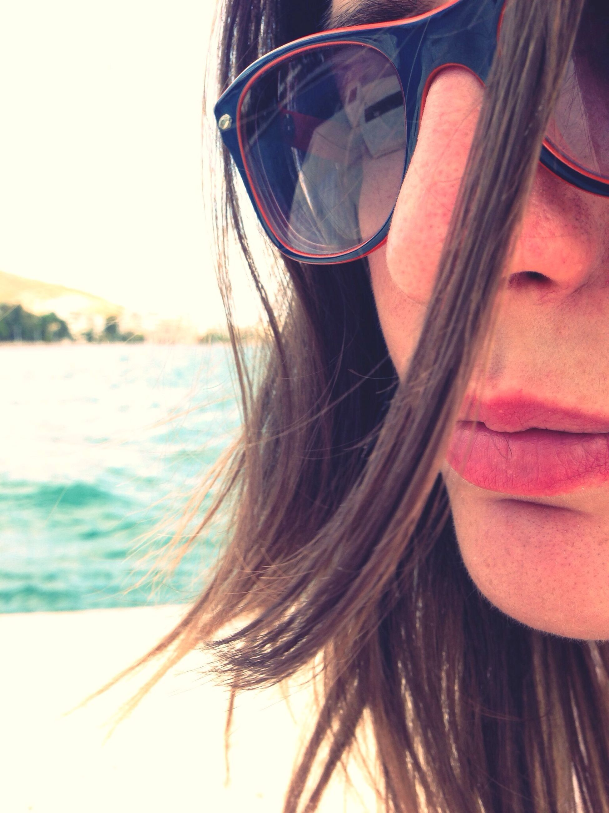 water, young adult, lifestyles, leisure activity, headshot, sea, young women, long hair, person, sunglasses, focus on foreground, vacations, close-up, beach, head and shoulders, brown hair