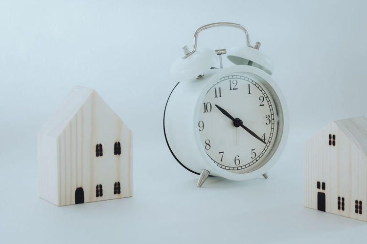 Close-up of clock against white wall