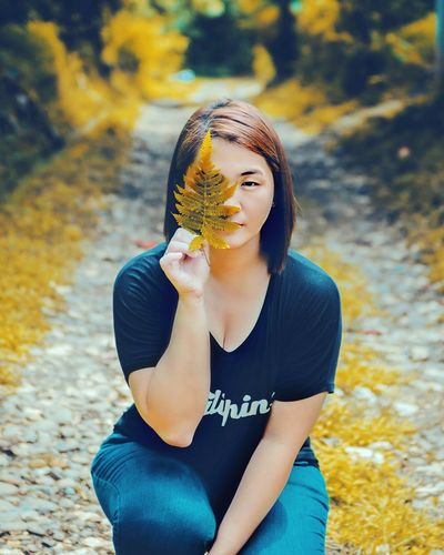 Portrait Of Young Woman Holding Autumn Leaf On Footpath