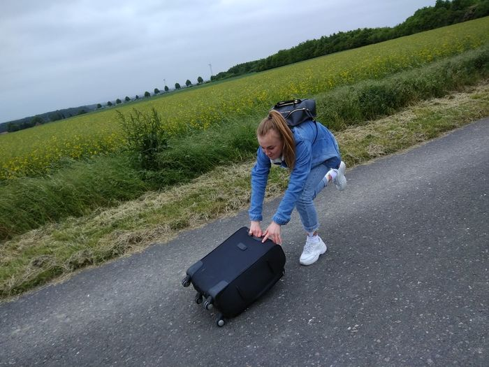 High angle view of teenage girl pushing luggage on road