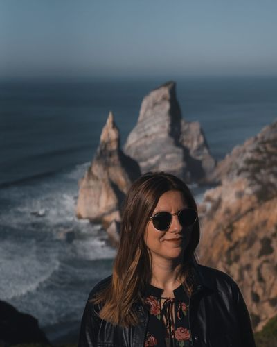 Portrait of young woman wearing sunglasses on rock