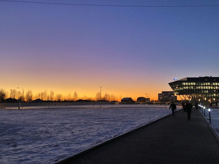 Sky Sunset Water Nature Architecture Clear Sky Beauty In Nature Built Structure Copy Space Scenics - Nature Real People Building Exterior Unrecognizable Person Cold Temperature Outdoors City Incidental People Tranquility Winter