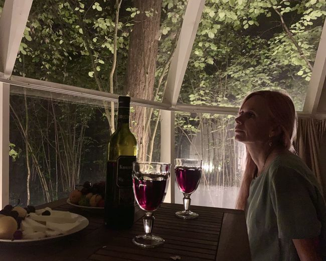 Woman drinking glass on table by window