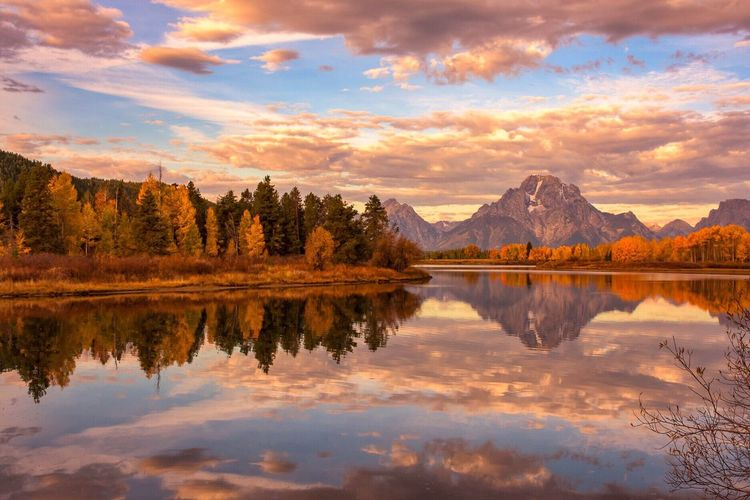 Reflection Of Trees And Mountains In Lake Against Cloudy Sky