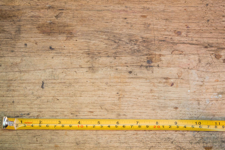 tape measure on the brown wooden background Home Industry Wood Work Building Design Directly Above Equipment Indoors  No People Ruler Table Tape Measure Tool Wall - Building Feature Wood - Material Work Tool Yellow