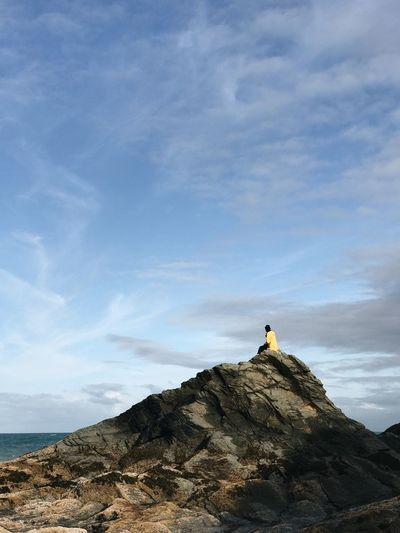 Distant view of woman relaxing on rock formation by sea against sky