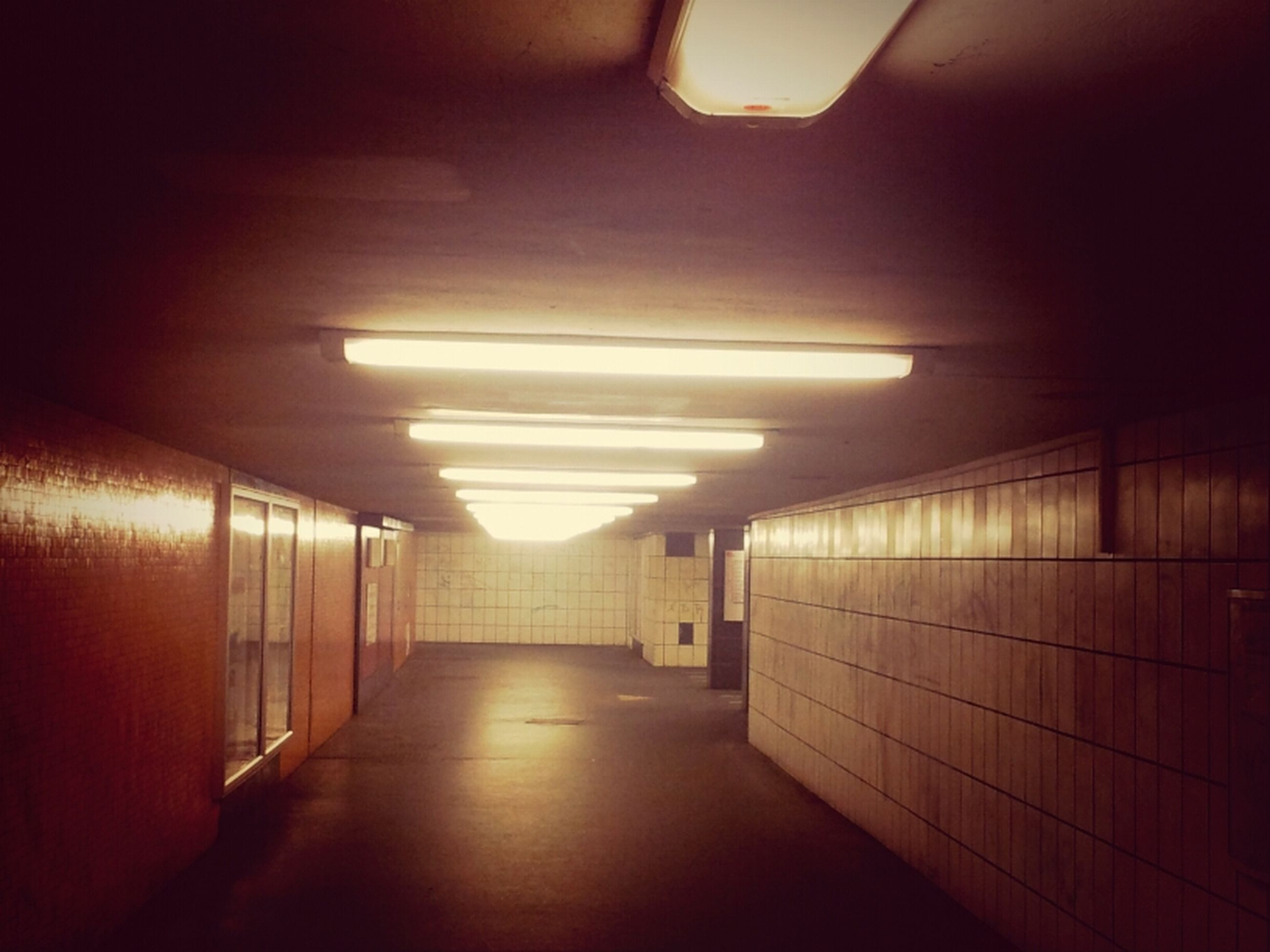 indoors, illuminated, the way forward, corridor, empty, ceiling, lighting equipment, architecture, built structure, absence, diminishing perspective, flooring, narrow, wall - building feature, long, interior, tunnel, subway, light - natural phenomenon, no people