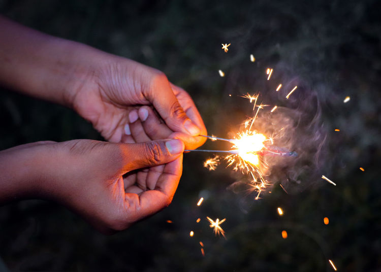 Close-up of person holding sparklers at night