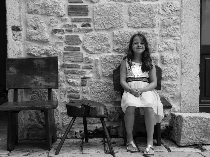 Portrait Of Girl Sitting On Chair Against Wall