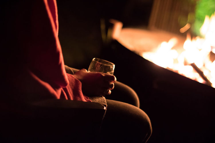 Midsection of woman holding glass by fireplace at home