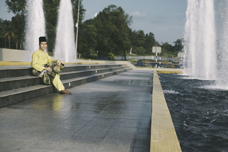 A man in Malay traditional costume Architecture Day Drinking Fountain Fountain Fountain Full Length Leading Lines Lifestyles Long Exposure Men Motion Nature One Person Outdoors People Real People Sky Splashing Spraying Tree Water Waterfall The Street Photographer The Street Photographer - 2017 EyeEm Awards Break The Mold