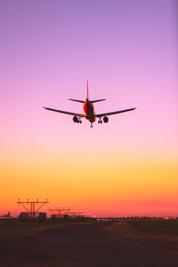 Low angle view of airplane flying against dramatic sky during sunset
