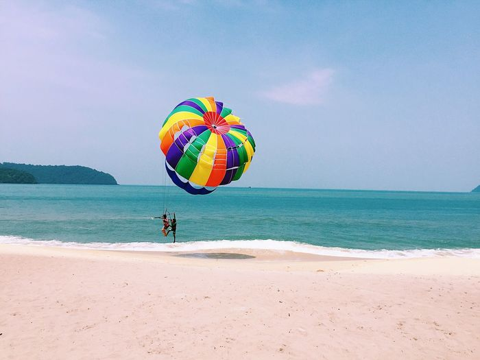 People parasailing over beach against sky