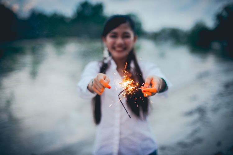 Smiling young woman standing on fire in water