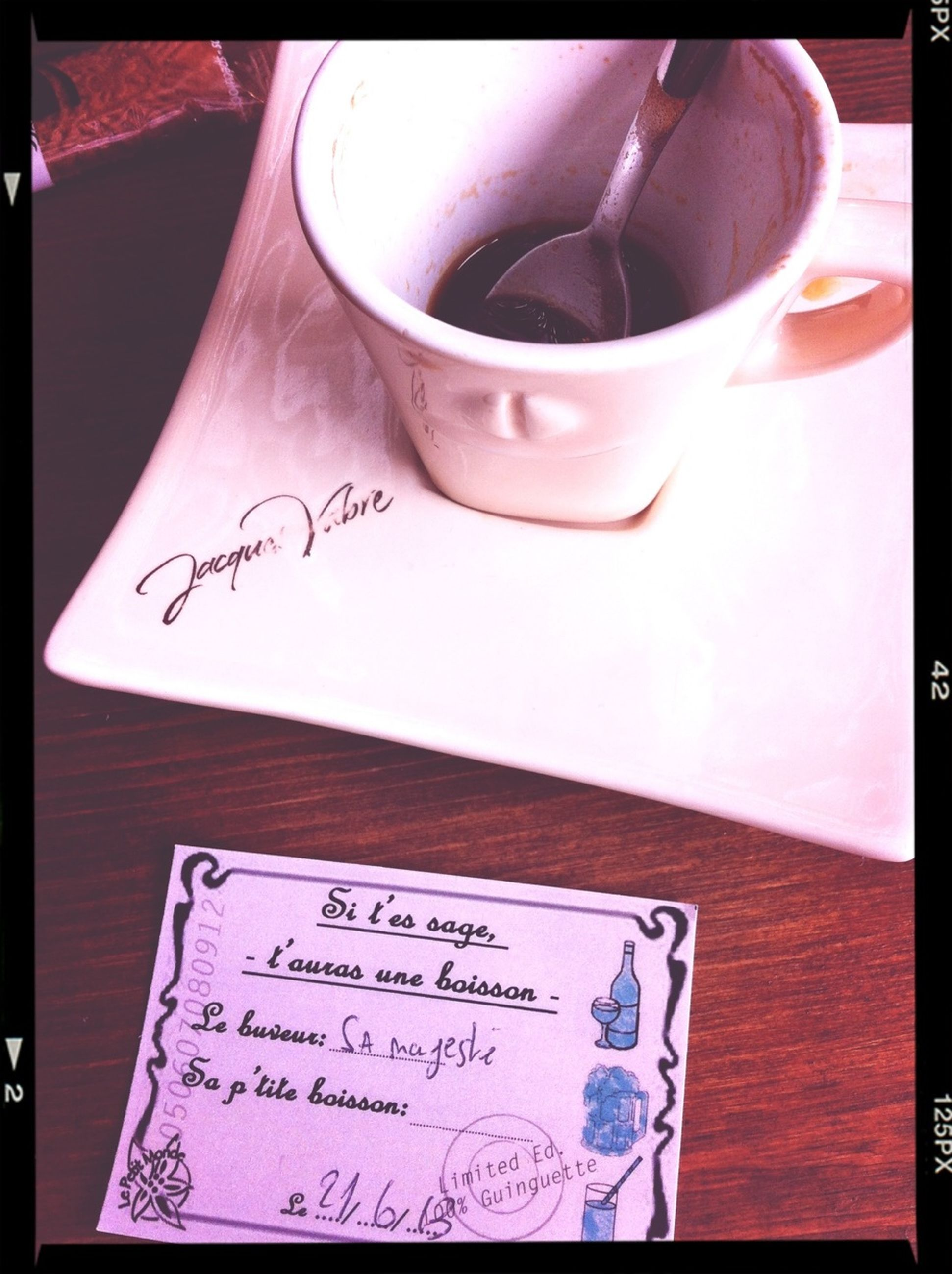 indoors, text, table, western script, transfer print, communication, food and drink, still life, close-up, auto post production filter, paper, freshness, book, drink, high angle view, refreshment, coffee cup, no people, handwriting, pink color