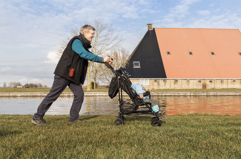 Grandfather Pushing Granddaughter While Sitting In Baby Stroller By Canal In City
