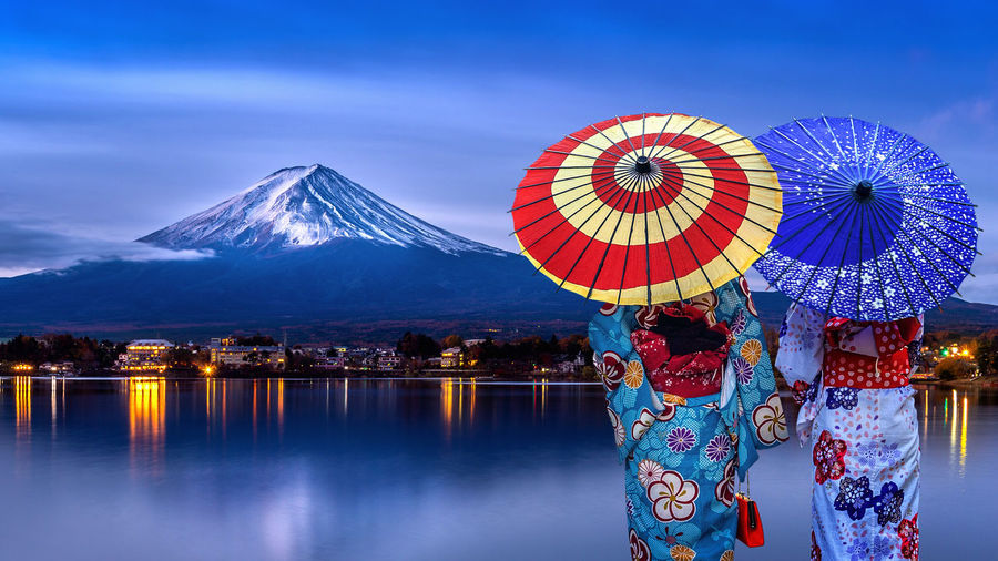 Asian womans wearing japanese traditional kimono at Fuji mountain, Kawaguchiko lake in Japan. Mountain Water Beauty In Nature Protection Sky Nature Snow Illuminated Scenics - Nature Cold Temperature Real People Umbrella Travel Destinations Blue Multi Colored Winter Architecture Reflection Outdoors Snowcapped Mountain