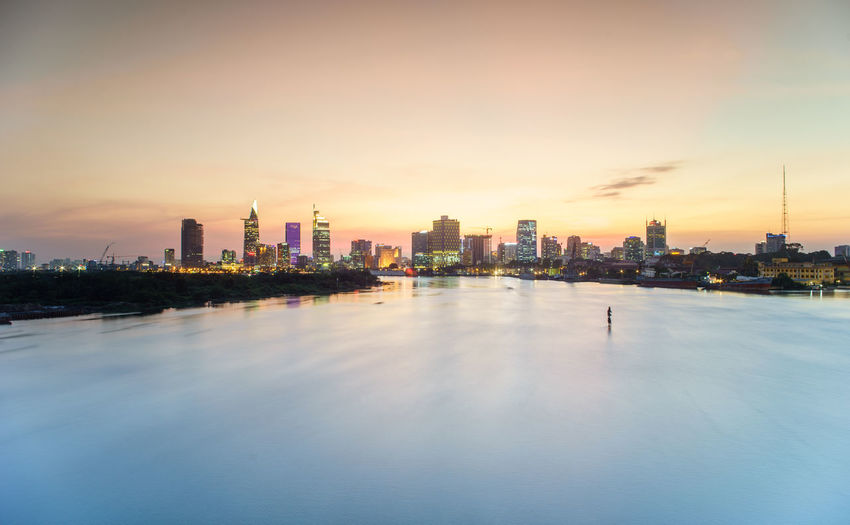 VIETNAM, FEBRUARY 01, 2016: Buildings along Saigon river in sunset Architecture ASIA Asian  City Cityscape Downtown District Finance No People Office Building Outdoors River View Riverside Saigon Sky Skyscraper Sunset Tree Urban Skyline Vietnam