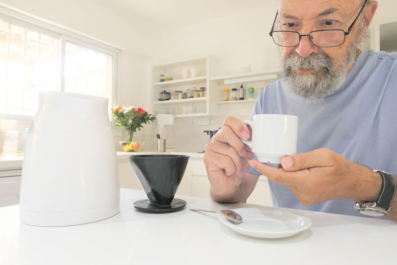 Midsection of man drinking coffee on table