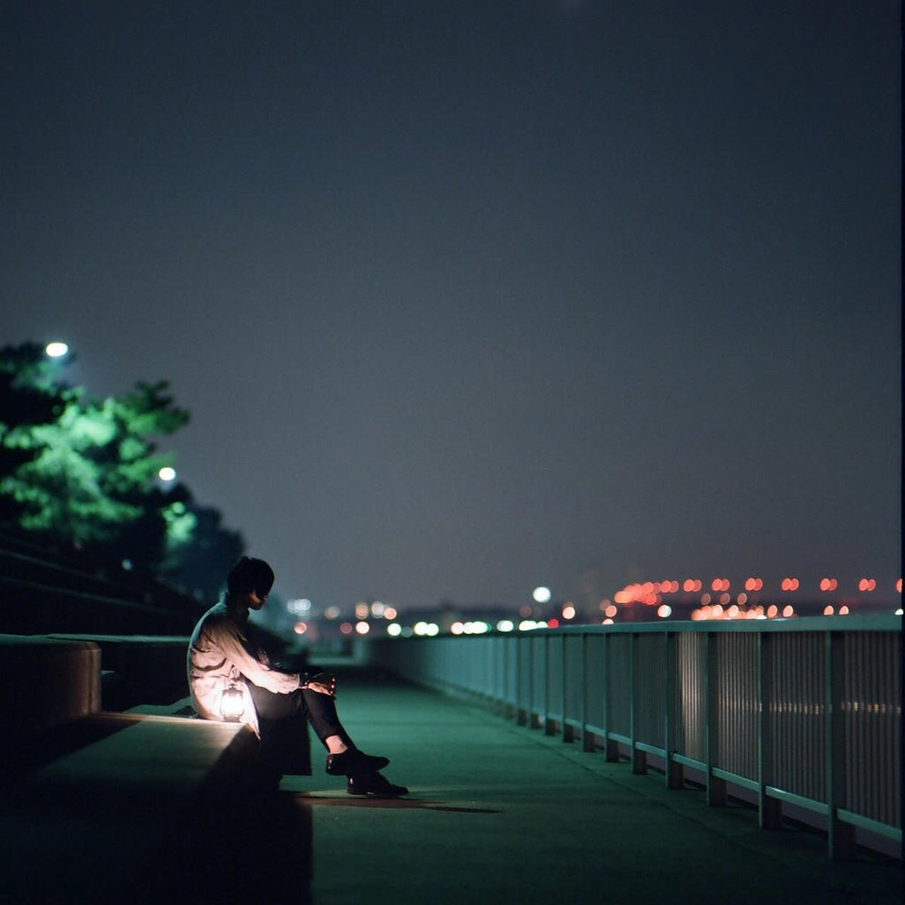 Lonely woman sitting on steps on sidewalk at night