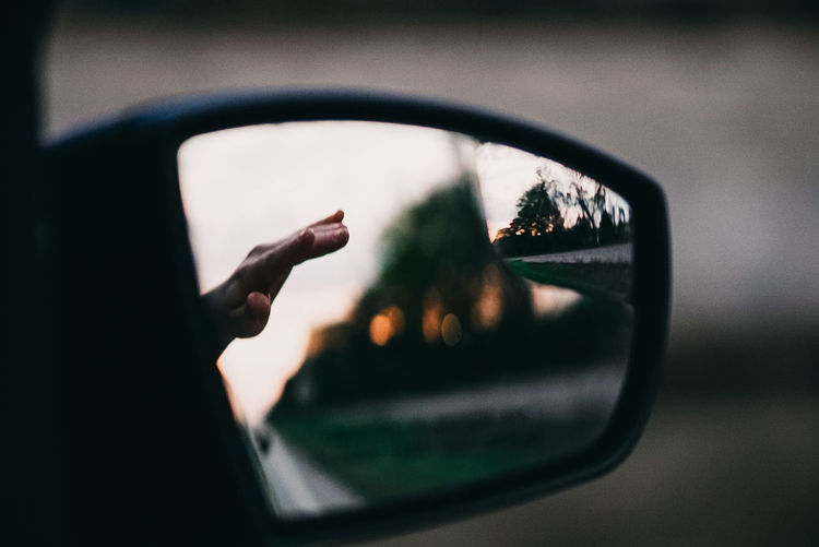 Close-up of hand out of car side-view mirror