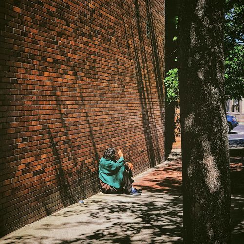 Man sitting against wall in city