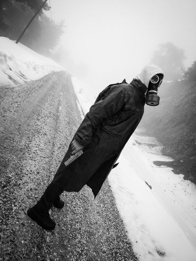 Side View Portrait Of Man Wearing Gas Mask While Holding Gun On Road During Winter