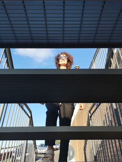 Low angle view of people on railing against sky