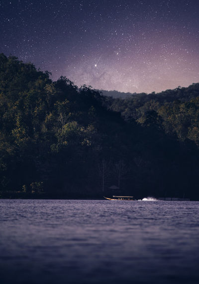 Scenic view of river by forest against sky at night