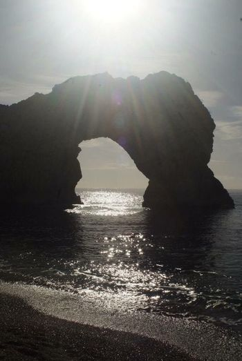Sun glancing through Durdle door arch Sea Water Rock Formation Nature Beauty In Nature Tranquility Rock - Object Scenics No People Waterfront Tranquil Scene Day Outdoors Sky Mountain Horizon Over Water Durdle Door Dorset Coast Uk
