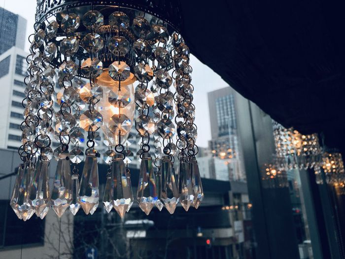 Low angle view of illuminated chandelier in city at night