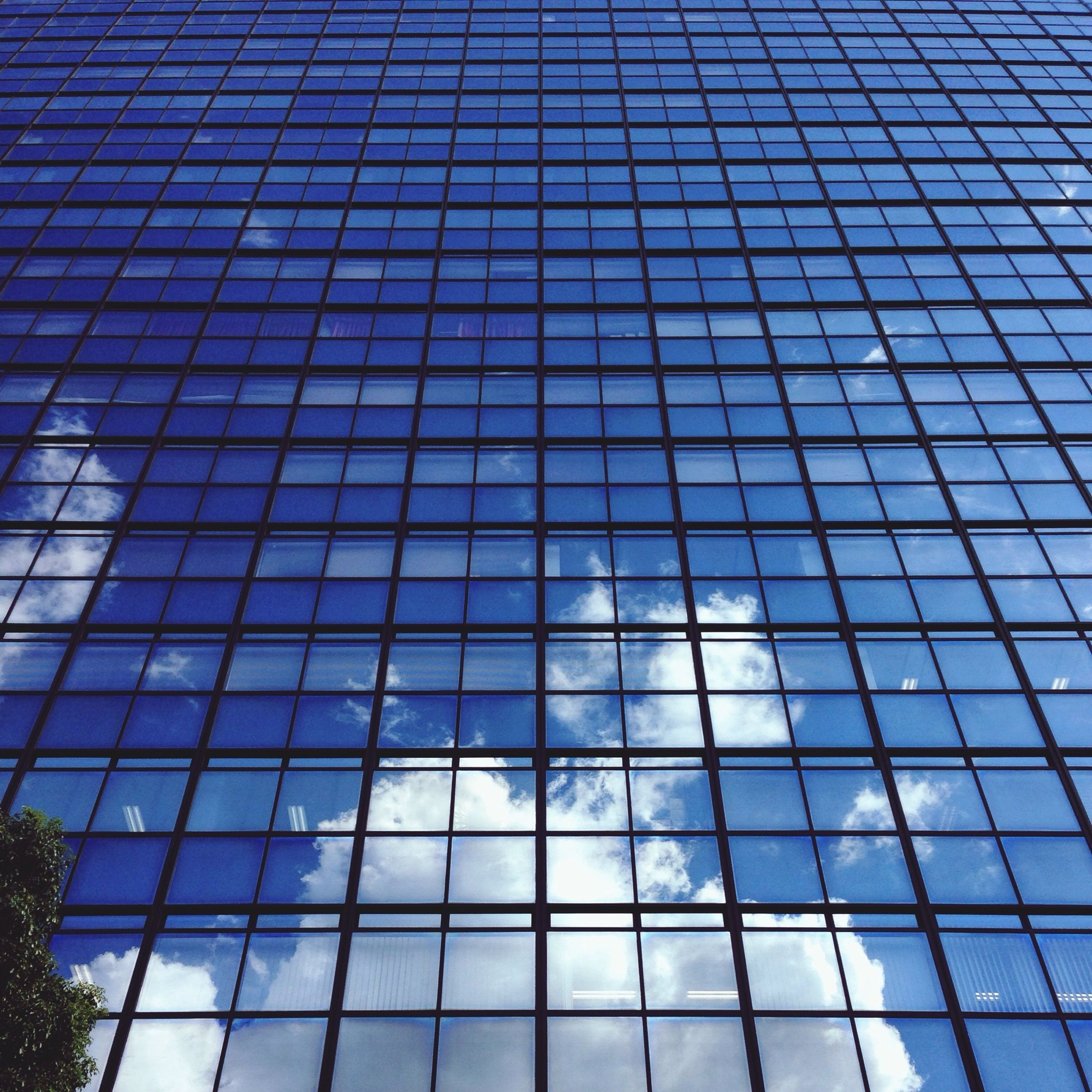 architecture, low angle view, built structure, building exterior, modern, glass - material, office building, reflection, city, skyscraper, tall - high, blue, tower, building, sky, pattern, day, architectural feature, window, no people