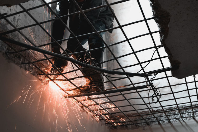 Low Angle View Of Manual Worker Welding Metal In Factory